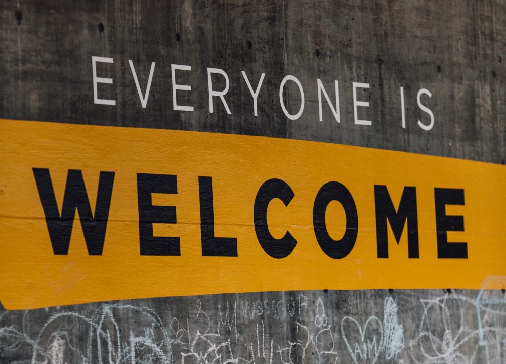 "A mural with the words ""Everyone is Welcome,"" with the first two letters in white and the final one in black on an ochre background. Posted to accompany CDP's blog post, Addressing the Unique Needs of Immigrants Before, During and After Disaster."