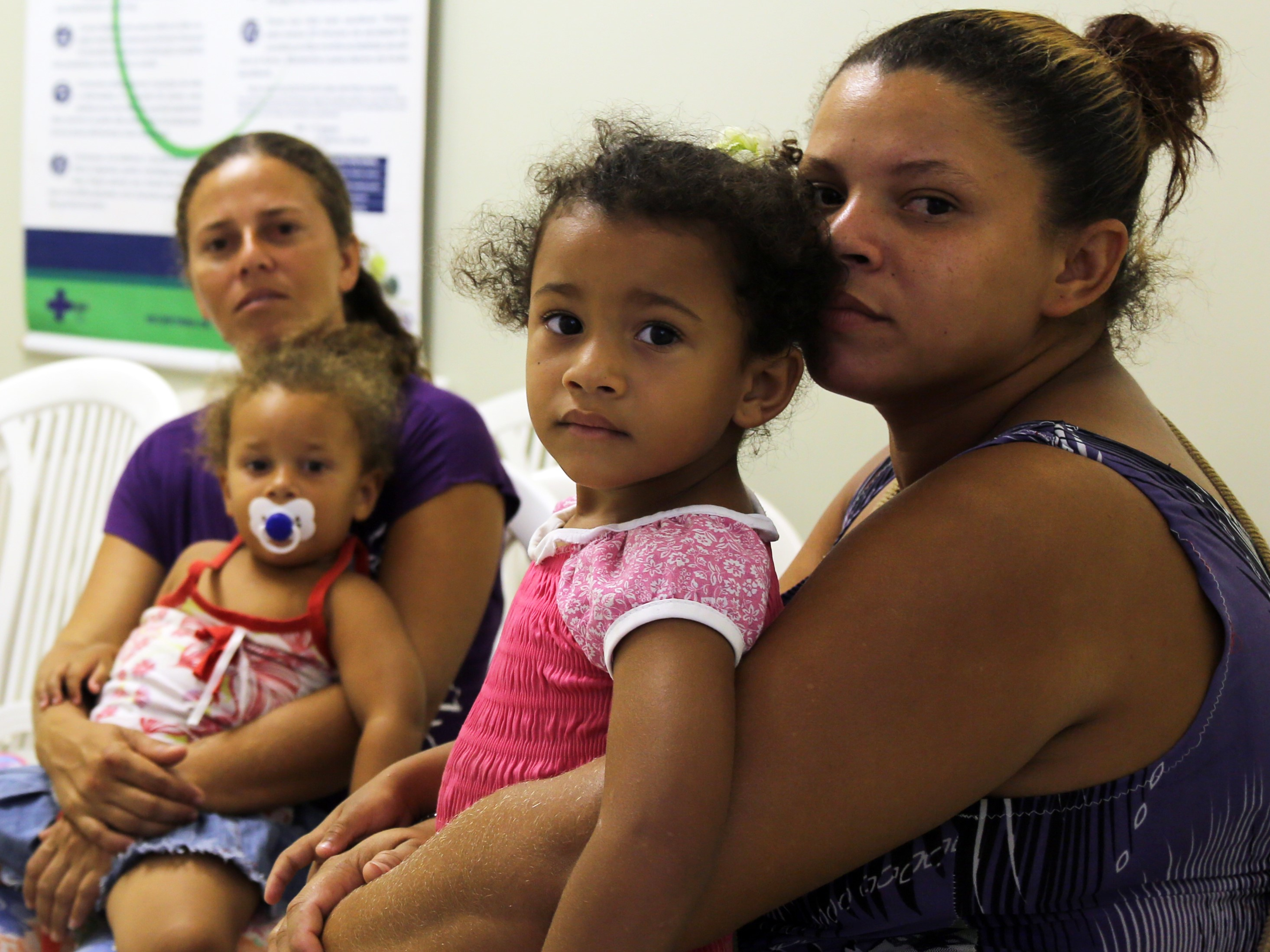 Two women with young girls on their laps, one with a pacifier, awaiting doctor's appointments in an office. Posted to accompany GCIR's brief and funding recommendations, Protecting Families and Advancing Belonging: How Philanthropy Can Answer Threats to the Well-Being of Immigrants.