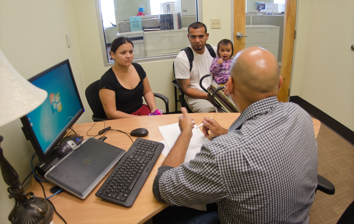 Male and female couple, with the former holding their daughter, seated in an office and speaking with a man who is seated behind a desk with his back to the camera. Posted to accompany GCIR's webinar, No Housing Support for Mixed Status Families? How Philanthropy Can Respond to Proposed HUD Rule.