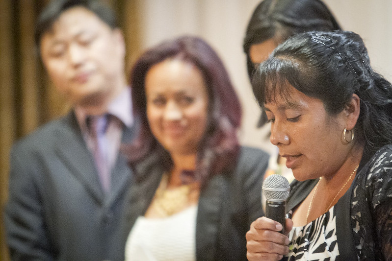 woman-speaking-into-microphone-with-people