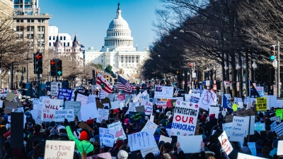 Shows a hundreds of people with signs and flags crowded onto a street in Washington, DC, in a protest against the Muslim ban. The Capitol building can be seen in the center distance. Posted to accompany GCIR's webinar, Movement Lawyering: Reimagining Lawyering before the Immigration System.