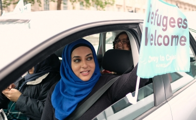 refugees-welcome-sign-held-by-woman-driving-car
