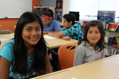 Two smiling girls at a desk in a classroom with two more students behind them. Posted in conjunction with GCIR's webinar, Monthly Immigration Policy Call: April.