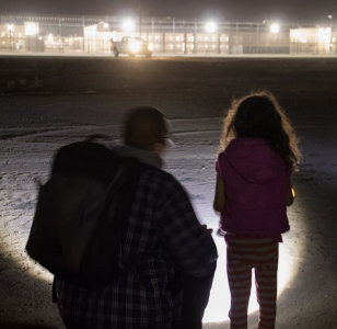 A showing a nighttime vigil with a young child and adult standing in front of a detention facility. Posted to accompany GCIR's webinar, A Primer on Divesting from Immigrant Detention.