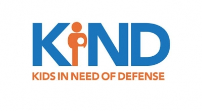The Kids in Need of Defense logo, which spells out KIND in large blue letters, with a orange figure as the 'i' and the organization's full name below in orange. Posted in relation to their report, Blocked From Safety: Unaccompanied Children along the U.S.-Mexico Border.