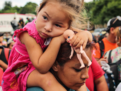 A child on her mother's shoulders in a crowd of migrants waiting to board a caravan. Accompanies GCIR's resource, GCIR 2018 Annual Report: Uniting Philanthropy in Polarizing Times.